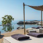 Infinity pool sun loungers with towels and Aegean sea view